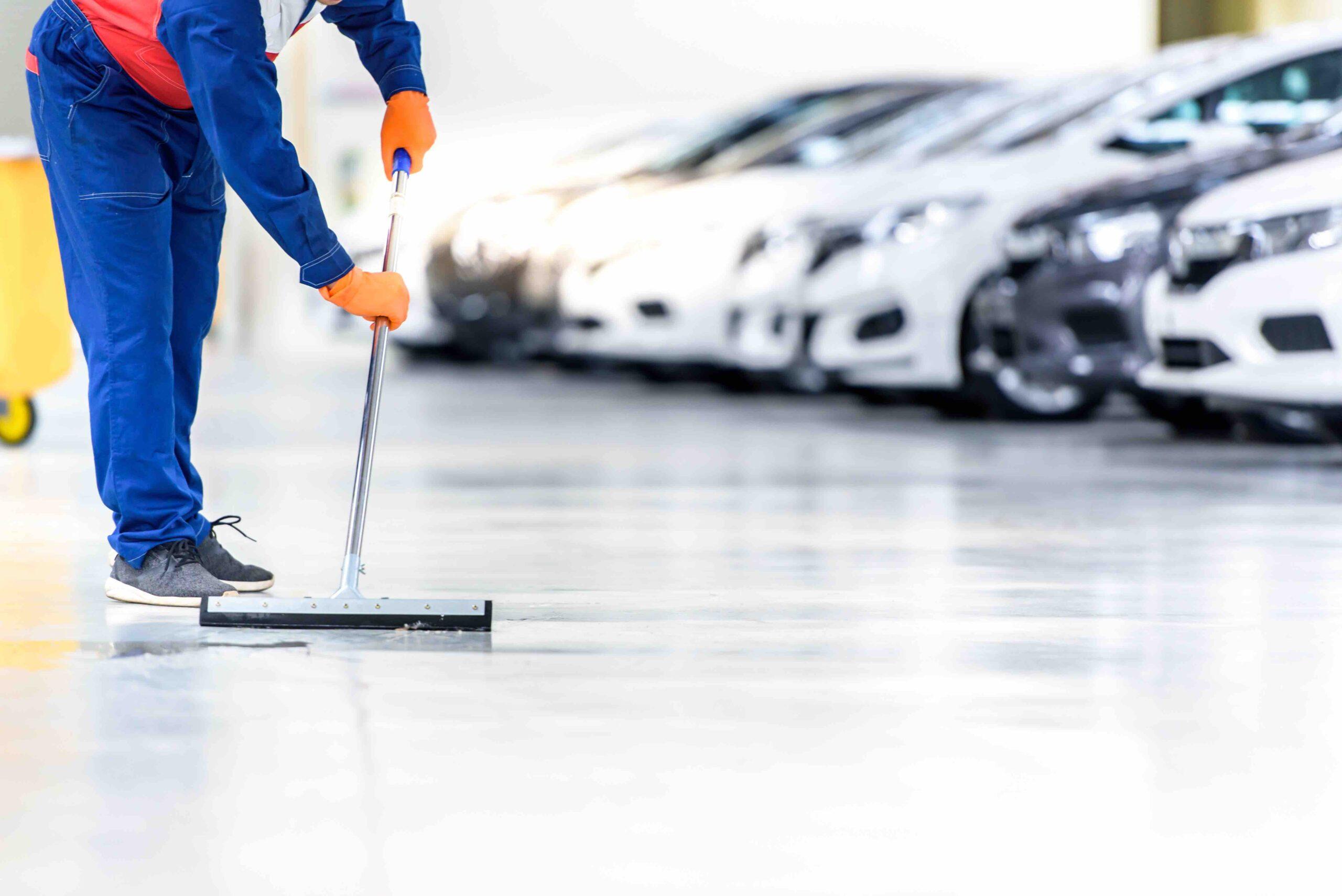 Rengøringsassistent vasker gulv hos en bilforhandler. Rengøringskoncept for butikker.